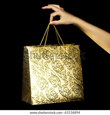 Woman hand with golden holiday bag