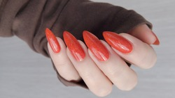 Woman hand with long nails and orange ginger manicure holds a bottle of nail polish