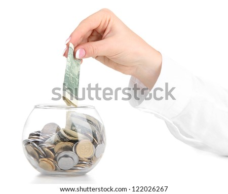 Woman hand with money in glass jar isolated on white