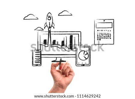 woman hand with pencil draws Rocket launch from PC monitor. PC monitor and tablet and smart phone width business chart on office desk. Concept of business start-up, boost or success #1114629242