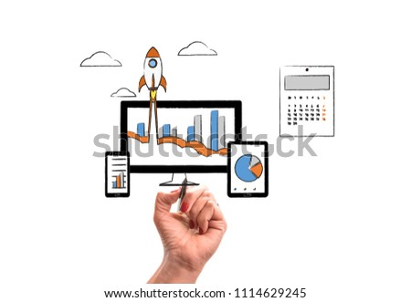 woman hand with pencil draws Rocket launch from PC monitor. PC monitor and tablet and smart phone width business chart on office desk. Concept of business start-up, boost or success #1114629245