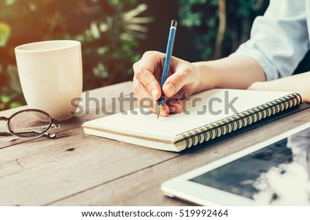 Woman hand with pencil writing on notebook at coffee shop. Woman working in outdoor at coffee shop.