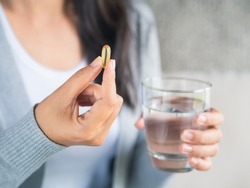 Woman hand with pills medicine tablets and glass of water in her hands. Healthcare, medical supplements concept