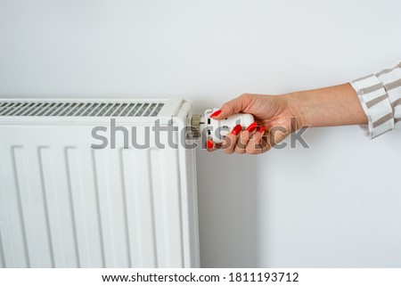 Woman Hand with Red nail laquer Adjusting The Knob Of Heating Radiator. The valve from the radiator - Heating. Hand adjusting thermostat valve of heating radiator in a room on white background.