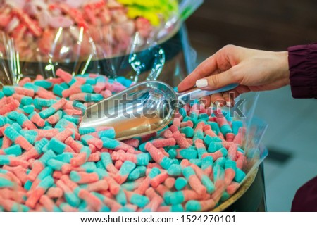 Woman hand with scoop taking colorful delicious marmalade jelly candies on counter of shop, grocery, market, cafe. Dessert, sale, sweet food and confectionery concept