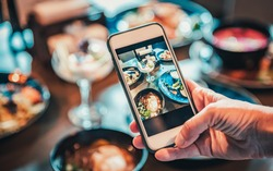 woman hand with smartphone photographing food at restaurant or cafe