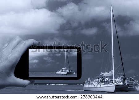 Woman hand with smartphone taking a picture of Catamaran on open ocean.