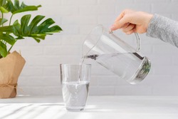 Woman hand with transparent jug fills a glass pure drinking water, creating air bubbles, green plant leaf on white table at home. Freshness, cold refreshing drink, water balance, health, thirst, diet.