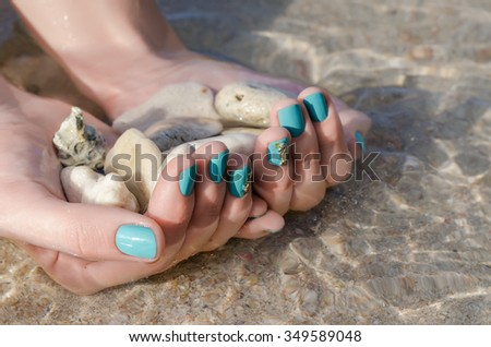 Woman hand with turquoise nail design and sea stones. Clean sea water.