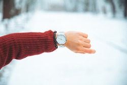 woman hand with watch on wrist winter snowed park on background