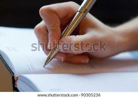 Woman hand writes on a paper