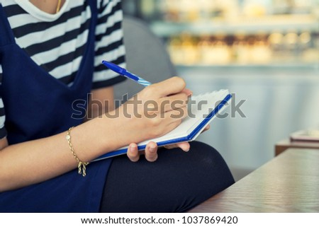 Woman hand writing check list on notebook, memo planning concept. #1037869420