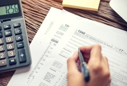 Woman hand writing U.S. tax form 1040, using calculator Individual income tax return, taxation without representation, time to payment concept.