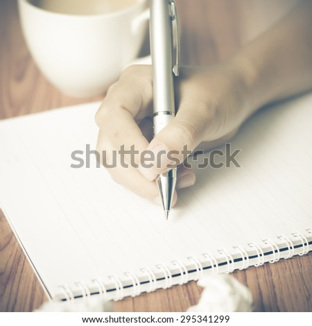 woman hand writing with pen on notebook.there are crumpled paper and coffee cup on wood table background vintage style