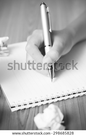 woman hand writing with pen on notebook.there are crumpled paper and coffee cup on wood table background black and white color tone style