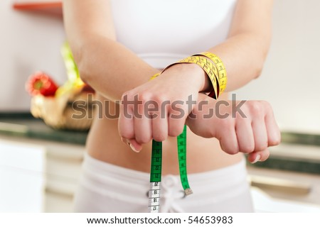 Woman handcuffed by a tape measure - symbol for eating disorder