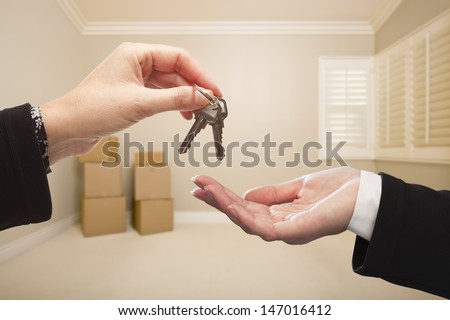 Woman Handing Over the House Keys To A New Home Inside Empty Tan Colored Room.