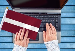 woman hands and flag of Latvia on computer, laptop keyboard