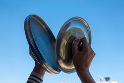 Woman hands banging pot lids against blue sky. Protest against the government measures. Banging pots and pans from the windows and balcony