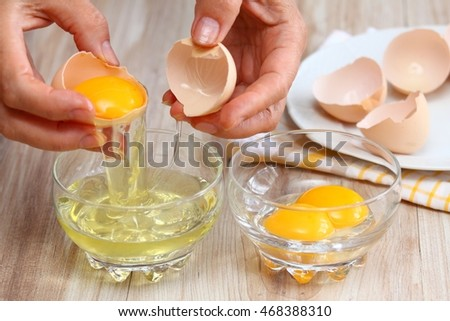 Woman hands breaking an egg to separate  egg white and  yolks and egg shells at the background   Сток-фото ©