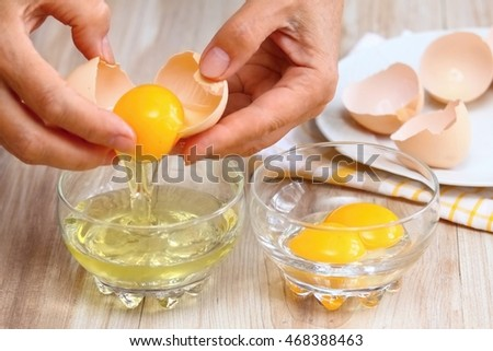 Woman hands breaking an egg to separate  egg  white and  yolks and egg shells at the background   #468388463
