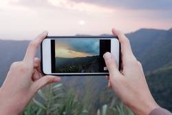 Woman hands capturing landscape of mountain view with smartphone