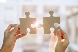Woman hands connecting couple puzzle piece against sunrise effect, businesswoman holding wood jigsaw with sunset background. Business solutions, target, success, goals and strategy concepts