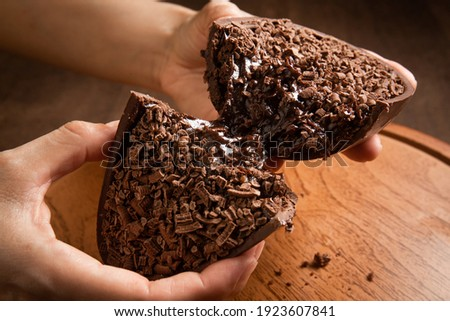 Woman hands crack a stuffed chocolate easter egg on a wooden stand on a wooden table stock photo