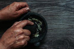 Woman hands crushing garlic with stone in a mortar on a wooden board, top view of traditional preparation in a mortar