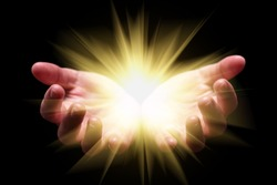 Woman hands cupped holding, showing, or emanating bright, glowing, radiant, shining light. Emitting rays or beams expanding. Religion, divine, heavenly, celestial concept. Black background, front view