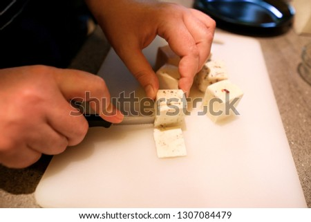 Woman hands cutting piece of cheese, she prepare food at kitchen. Chef cutting cheese with knife on wooden board on restaurant kitchen table. Housewife with a knife sliced cheese on cutting board. #1307084479