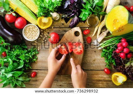 Woman hands cutting vegetables on wooden background. Cooking ingredients, top view, copy space, flat lay