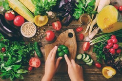 Woman hands cutting vegetables on wooden background. Vegetables cooking ingredients, top view, copy space, flat lay