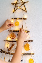 Woman hands decorating handmade craft Christmas tree made with natural materials and lights hanging on wall. Sustainable Christmas, zero waste, plastic free, eco friendly.