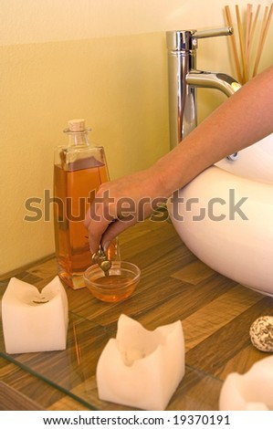 Woman hands filling up body massage oil in a small pot