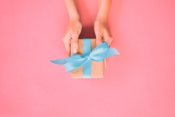 Woman hands give wrapped valentine or other holiday handmade present in paper with blue ribbon. Present box, decoration of gift on pink table, top view with copy space.
