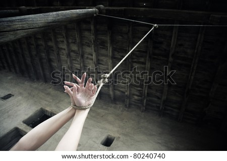 Woman hands hanged on the rope in ancient exterior