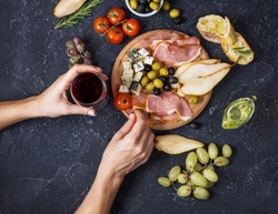 Woman hands hold a glass of wine. Appetizer, italian antipasto, ham, olives, cheese, bread, grapes, pear on dark stone background. Top view