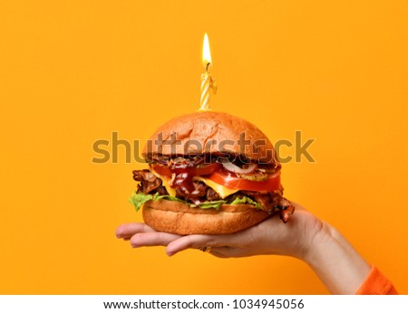 Woman hands hold big burger barbeque sandwich with beef and lit candle for birthday party on yellow background