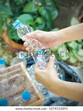 Woman hands hold plastic bottle garbage from wooden box to crushed and crumpled then put in  black plastic bag for concept reuse and recycle