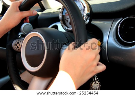 Woman hands holding a car steering wheel