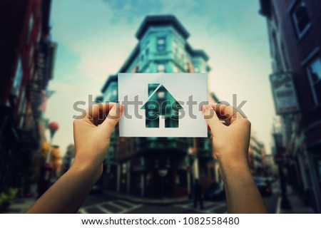 Woman hands holding a paper sheet with house icon inside in the middle of the street of a big city. Finding the ideal place for home. Property insurance concept.
