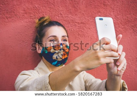 Woman hands holding a phone with the woman on the background doing a video call and wearing a reusable mask against coronavirus. Selective focus. Zdjęcia stock ©