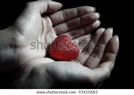 Woman hands holding a small heart as a symbol of love