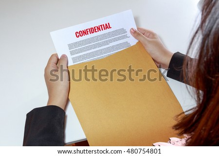 Woman hands holding and looking at confidential document in envelope - business concept.