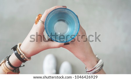 Woman hands holding blue glass of water