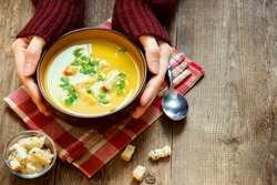 Woman hands holding bowl of vegetable soup with parsley and croutons over wooden background - healthy winter vegetarian food