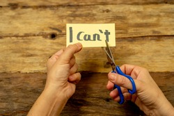 Woman hands holding card with written text i can't do it cutting the letter T with scissors so you read I can in Success and Challenge concept Believe in yourself and Motivation to achieve results.