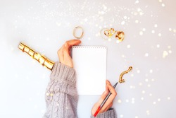 Woman hands holding clear white notebook, golden sparkles, new year, flat lay.