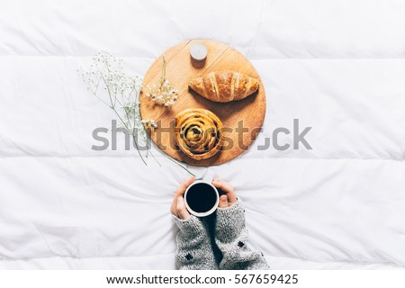 Woman hands holding cup of coffee in bed. Top view of breakfast in bed #567659425